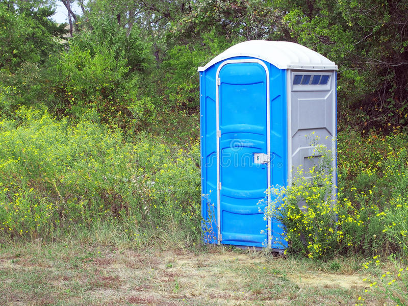 porta-potty-sitting-outdoor-setting-edge-meadow-front-trees-wildlife-area-45068183